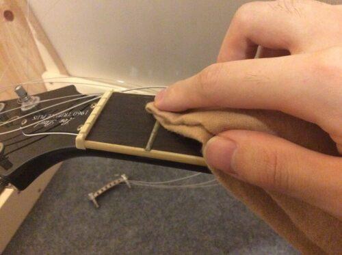 フレットをギタークロスで乾拭きする様子