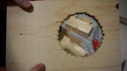 木の板にドリルで丸い穴を開けた様子
